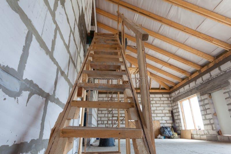 Interior do apartamento durante a renovação inferior, escadas de madeira da remodelação e da construção ao segundo andar imagens de stock