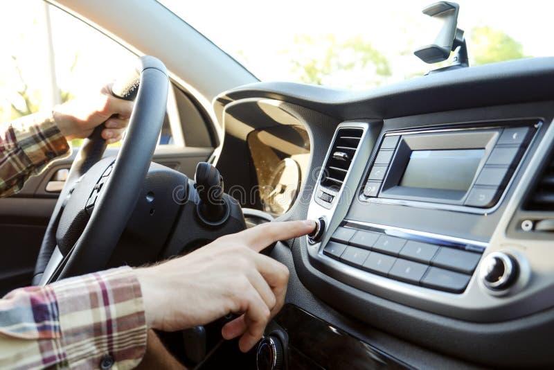 Interior do carro com o motorista masculino que senta-se atrás da roda, luz macia do por do sol Painel luxuoso e eletrônica do ve fotografia de stock royalty free