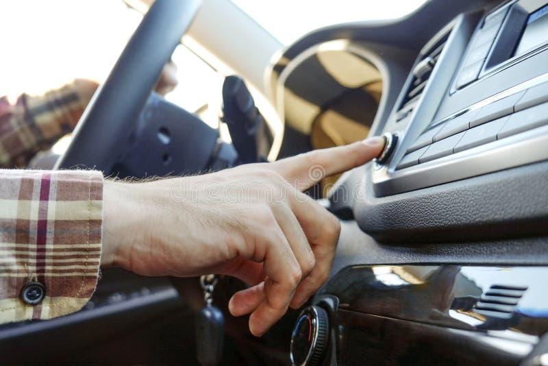 Interior do carro com o motorista masculino que senta-se atrás da roda, luz macia do por do sol Painel luxuoso e eletrônica do ve fotografia de stock