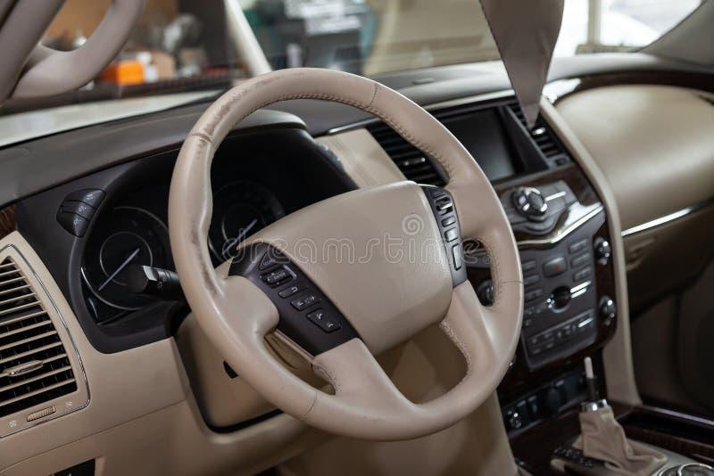 Interior do carro com um close-up de couro bege do volante que seja apagado em processo da restauração da operação e das necessid imagens de stock royalty free