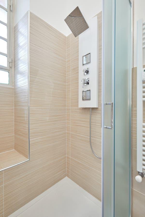 Interior do chuveiro com a coluna do chuveiro no apartamento renovado imagens de stock