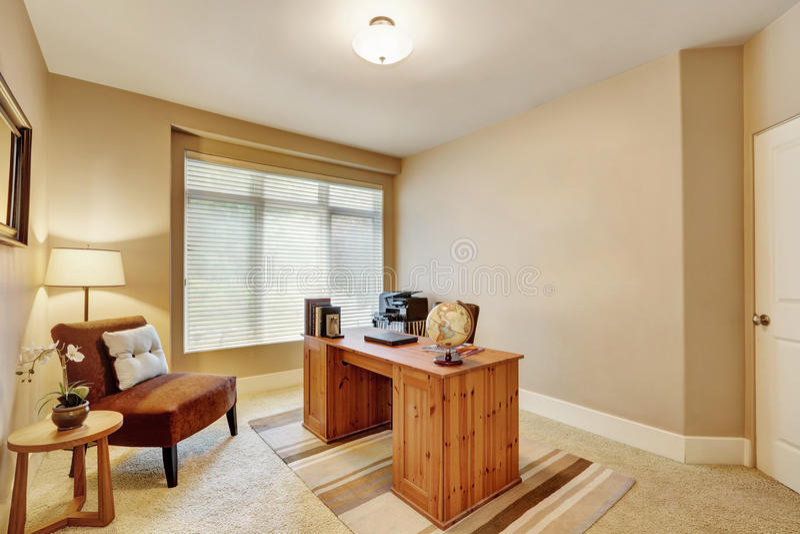 Interior do escritório domiciliário com paredes bege e a mesa de madeira fotografia de stock