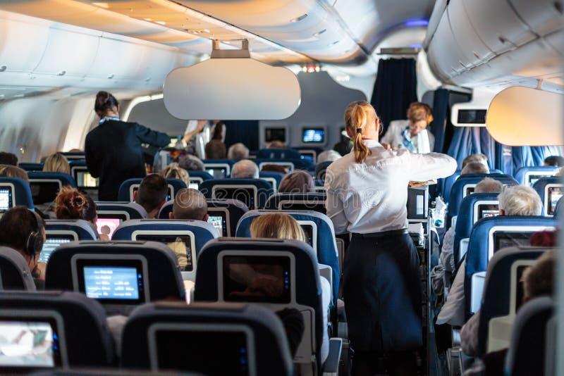 Interior do grande avião comercial com as comissárias de bordo que servem passageiros em assentos durante o voo imagem de stock