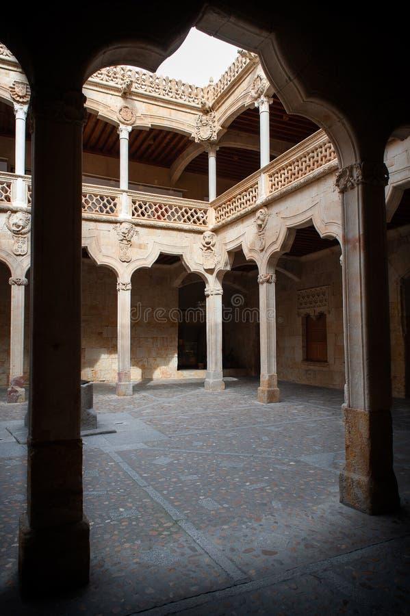 Interior do pátio com os mixtilineos dos arcos no primeiro plano, pertencendo à casa dos escudos, Salamanca, Espanha imagens de stock royalty free