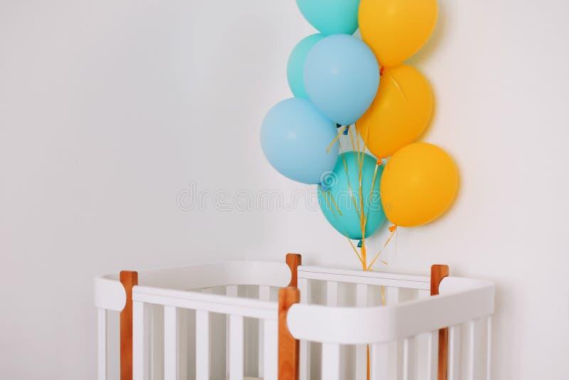 Interior do quarto do beb? Interior da sala do bebê de Minimalistic Balões festivos na frente da cama de bebê Conceito da celebra fotos de stock royalty free