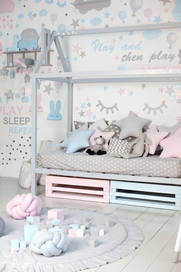 Interior do quarto de criança com brinquedos Design escandinavo de um quarto para crianças com cama de madeira em forma de casa,  imagens de stock royalty free
