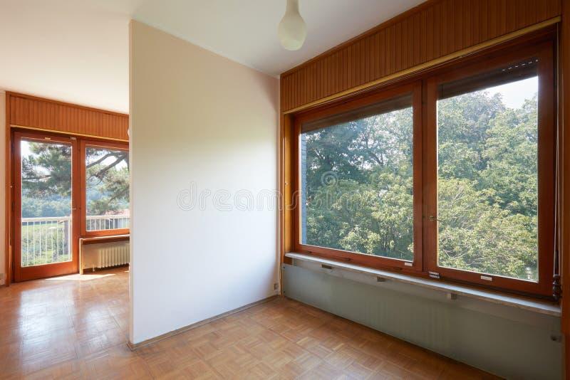 Interior do quarto duplo com o assoalho de madeira na casa de campo foto de stock