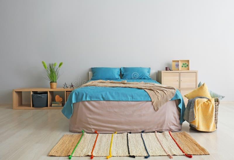 Interior do quarto moderno com a cama confortável perto da parede leve fotografia de stock royalty free