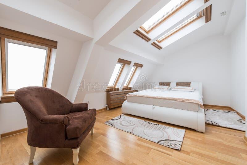 Interior do quarto no sótão luxuoso, sótão, apartamento com vento do telhado fotografia de stock royalty free