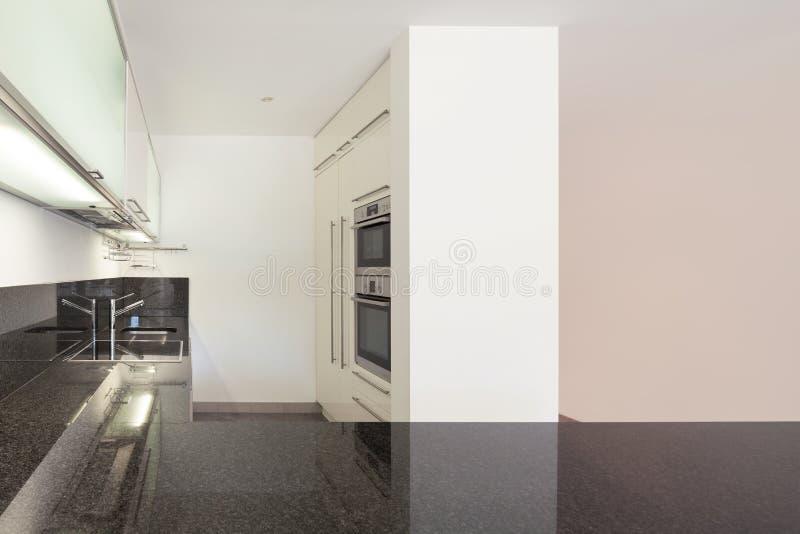 Interior, domestic kitchen. Interior of empty apartment, domestic kitchen, counter top black marble stock image