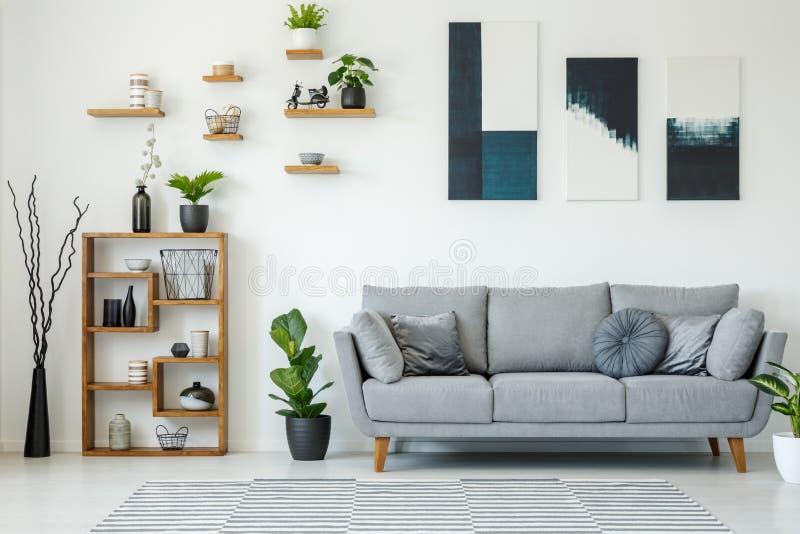 Interior elegante con un sofá gris, estantes de madera, p de la sala de estar imagen de archivo libre de regalías