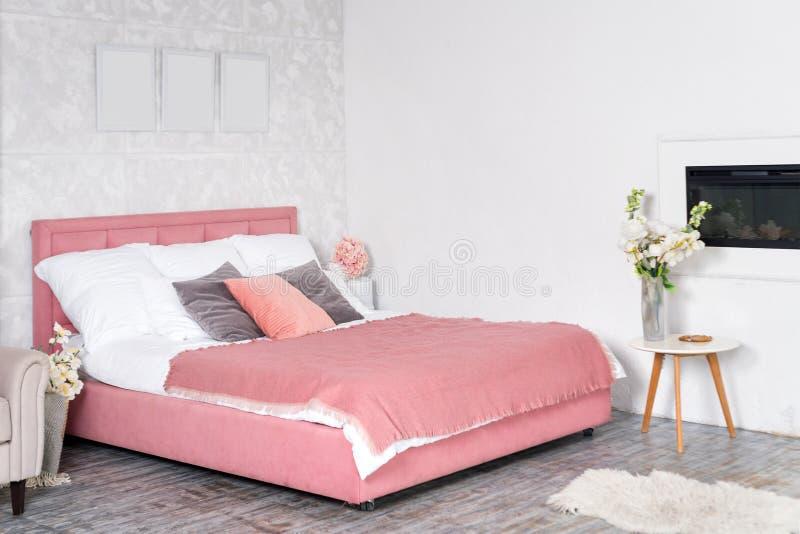 Interior elegante do quarto moderno Design branco e cor-de-rosa de um quarto confortável com flores cama de tamanho rei com rosa  imagem de stock royalty free