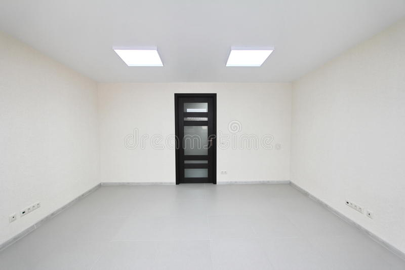 Interior empty office light room with white wallpaper unfurnished in a new building. Interior empty office light room with white wallpaper without furniture in a stock image