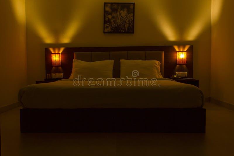 Interior encendido oscuro del dormitorio con las almohadas dobles y el tapiz de una choza en la pared blanca llana Iluminación ro fotos de archivo libres de regalías