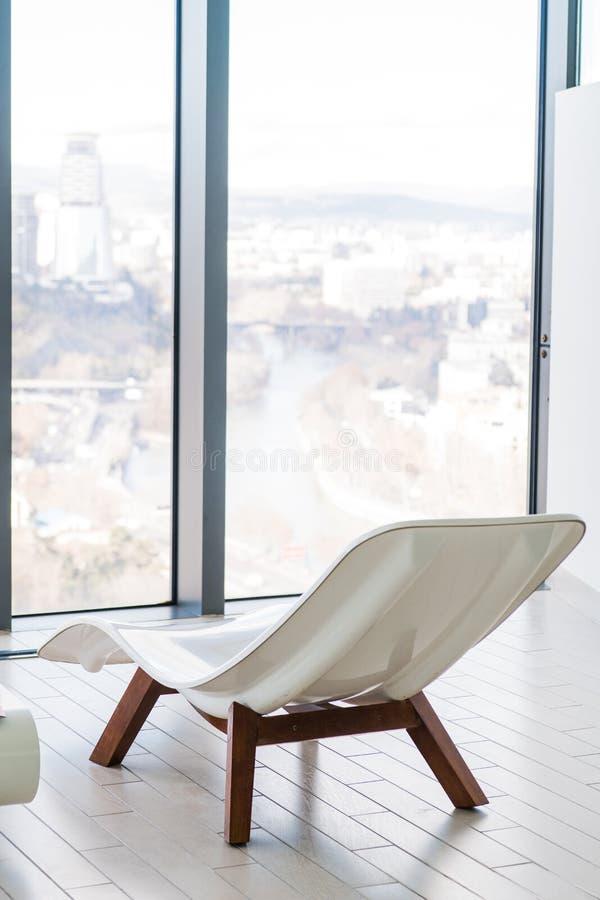 Interior ensolarado da associação pública com espreguiçadeira A cidade é vista através das grandes janelas fotografia de stock royalty free