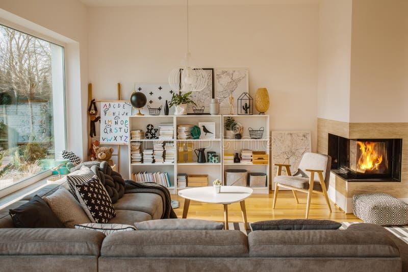 Interior escandinavo blanco de la sala de estar con la chimenea, carteles, imagen de archivo