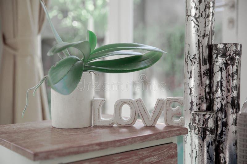 Interior escandinavo de Minimalistic con el sof? del dise?o, plantas tropicales, mesa de centro, muestra del amor imagenes de archivo