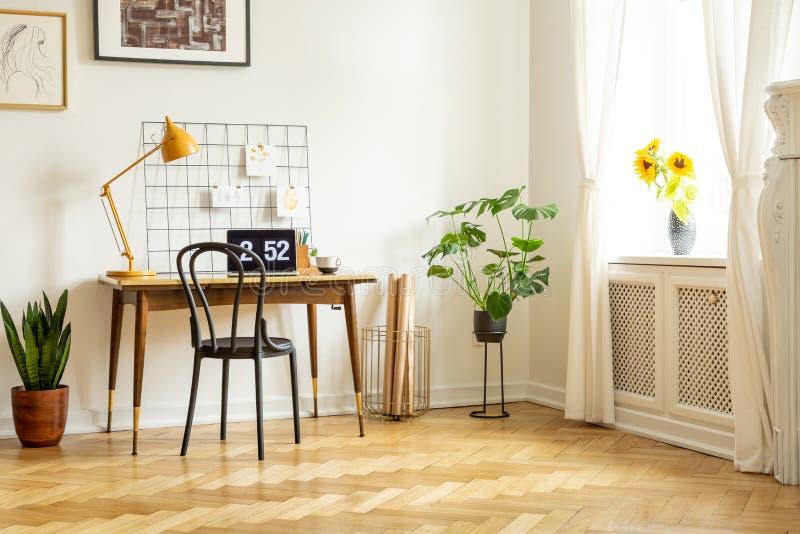 Interior espacioso de Ministerio del Interior con un escritorio, una silla, una lámpara amarilla, una planta y girasoles Foto ver imagen de archivo