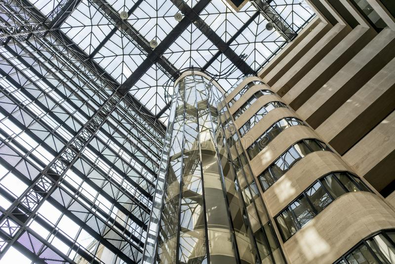Interior facade of modern building with glass elevator and balconies. stock image