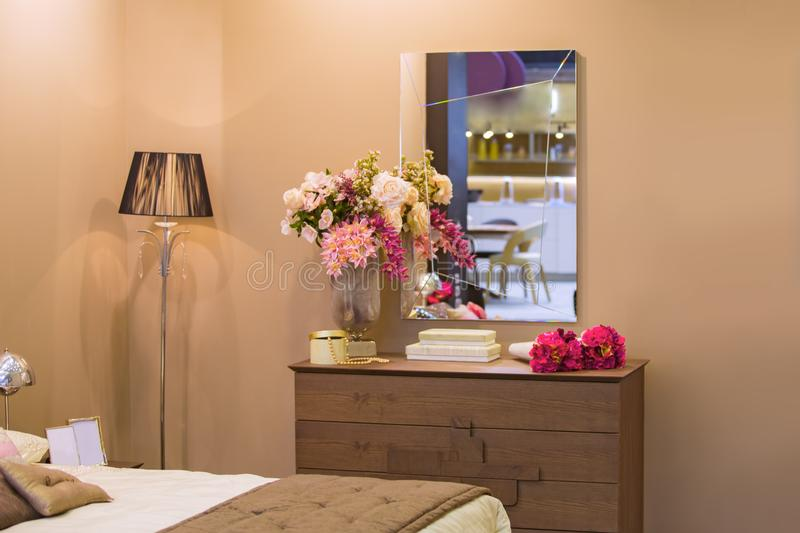 Interior of a female bedroom, beige walls, a wooden chest of drawers, flowers, decor, a gold floor lamp, a luxury mirror stock image