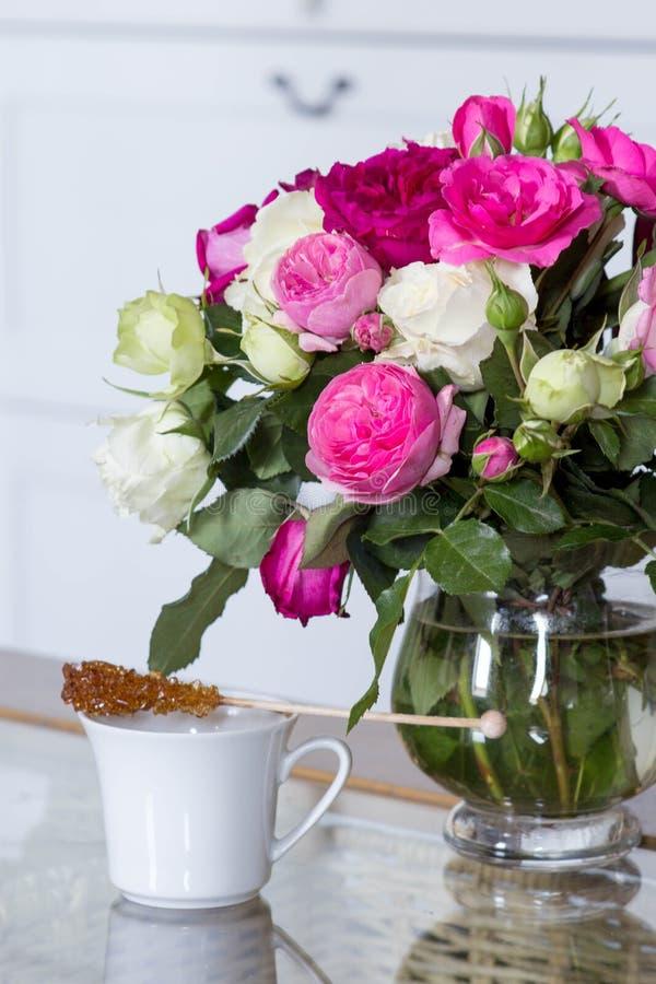 Interior femenino - ramo de rosas inglesas fragantes del rosa y blancas, cáscaras y vela rosada en la tabla de cristal fotos de archivo libres de regalías