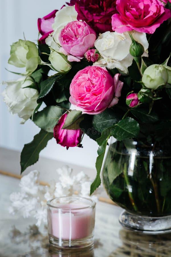Interior femenino - ramo de rosas inglesas fragantes del rosa y blancas, cáscaras y vela rosada en la tabla de cristal foto de archivo