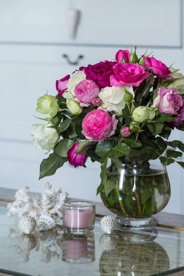 Interior femenino - ramo de rosas inglesas fragantes del rosa y blancas, cáscaras y vela rosada en la tabla de cristal imágenes de archivo libres de regalías