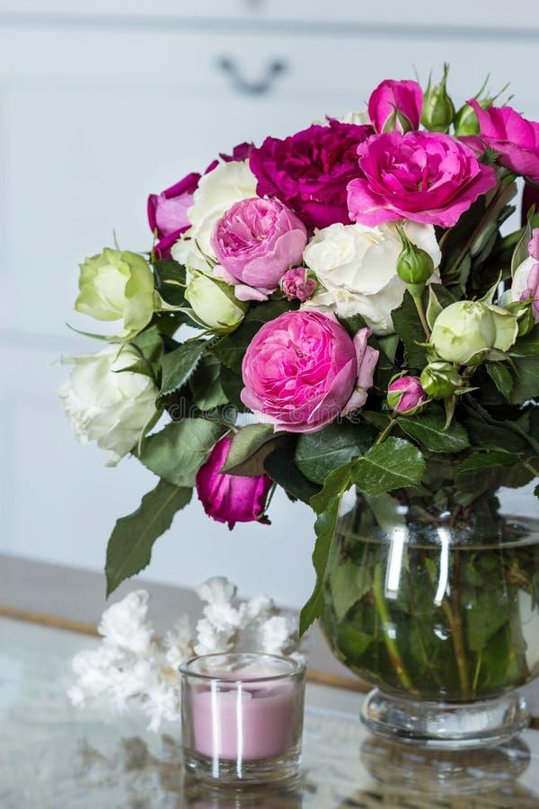 Interior femenino - ramo de rosas inglesas fragantes del rosa y blancas, cáscaras y vela rosada en la tabla de cristal fotografía de archivo libre de regalías