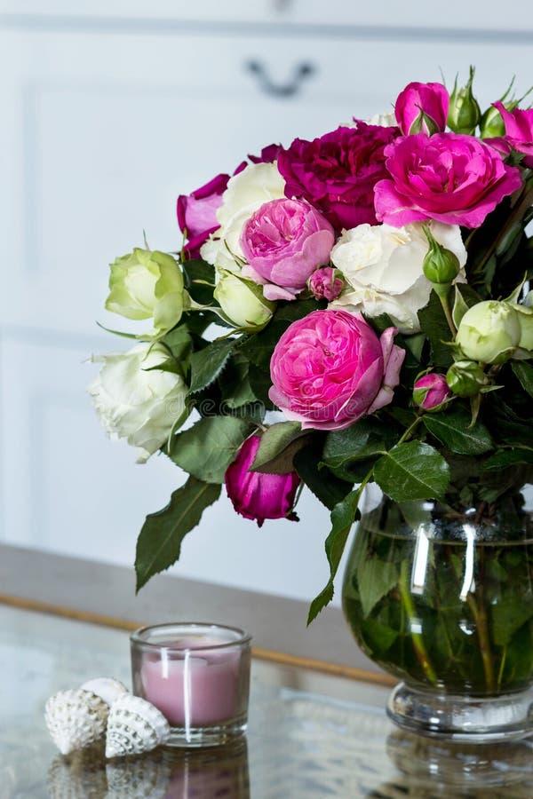 Interior femenino - ramo de rosas inglesas fragantes del rosa y blancas, cáscaras y vela rosada en la tabla de cristal imagenes de archivo