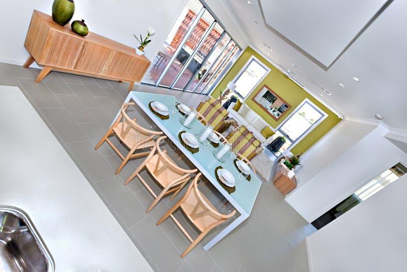 Interior grande moderno da sala de jantar com a tabela servida pronta para gues imagem de stock