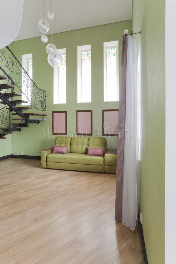 Interior in green and pink colors with green sofa and light parquet royalty free stock photos