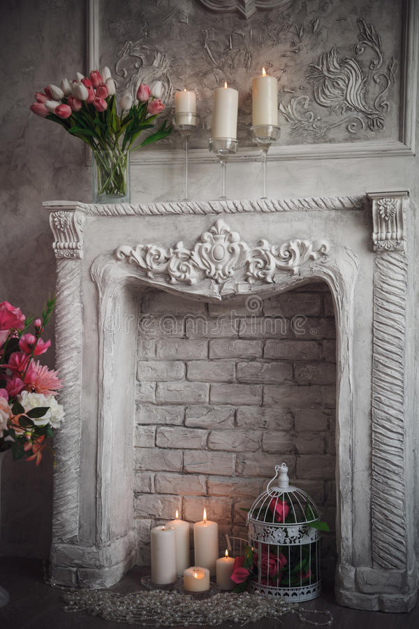 Interior with grey fretwork background, fireplace and flowers.  stock image
