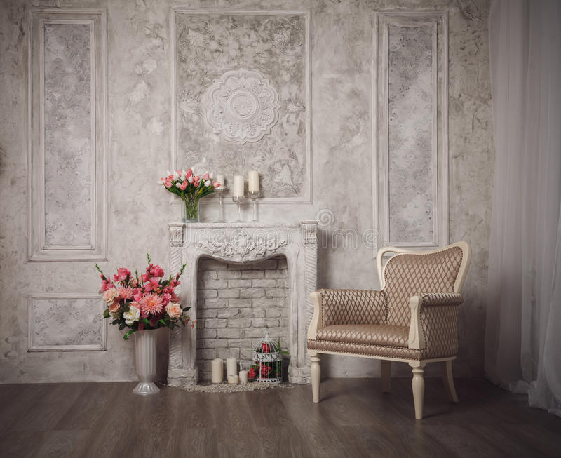 Interior with grey fretwork background, fireplace and flowers.  stock photo
