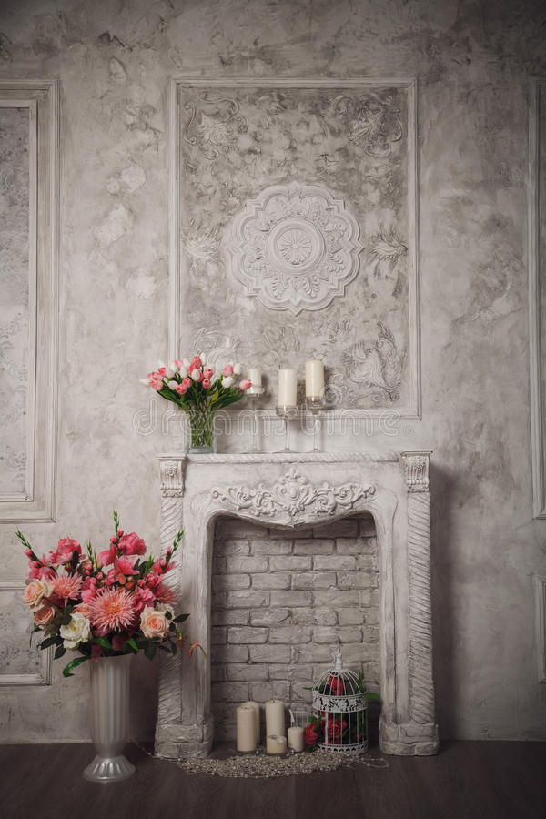 Interior with grey fretwork background, fireplace and flowers.  royalty free stock photography