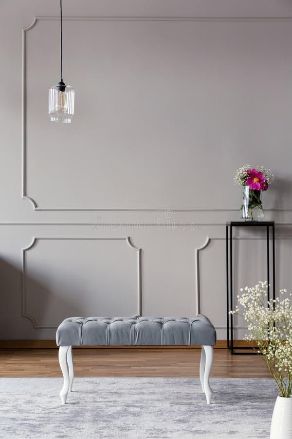 Interior gris del vestíbulo con un banco, una lámpara y una flor en un florero en un soporte Foto verdadera Lugar para su cartel fotos de archivo libres de regalías
