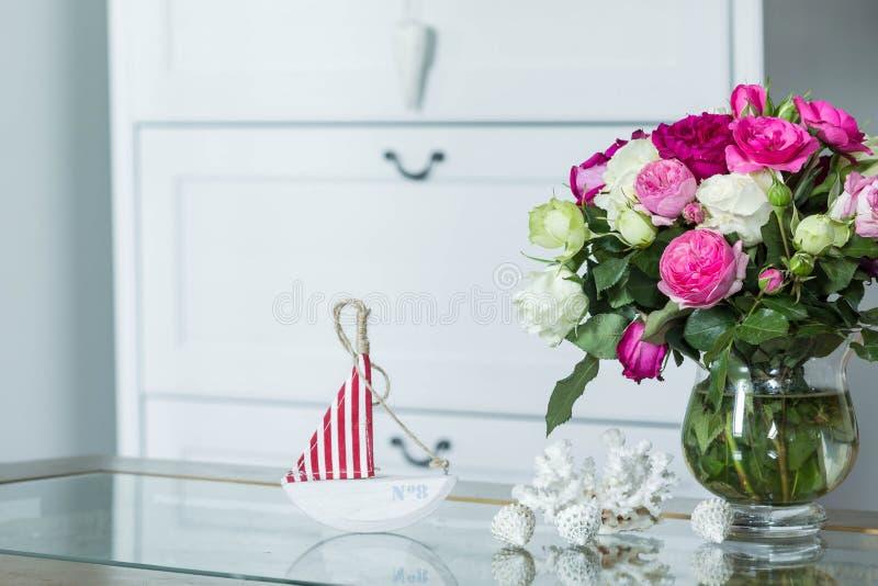 Interior in hampton style - fresh flowers, shells, sailboat decorations royalty free stock photos