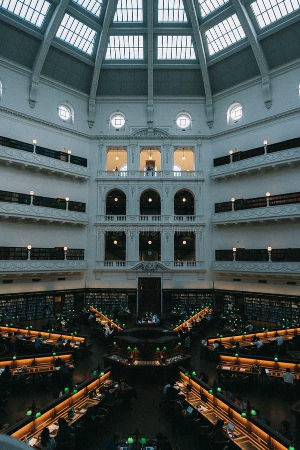 Interior hermoso de una biblioteca grande con la gente que trabaja en los ordenadores portátiles imagen de archivo libre de regalías