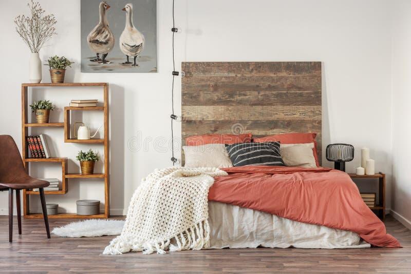 Interior hermoso del dormitorio con el cabecero de madera de la cama gigante imagenes de archivo