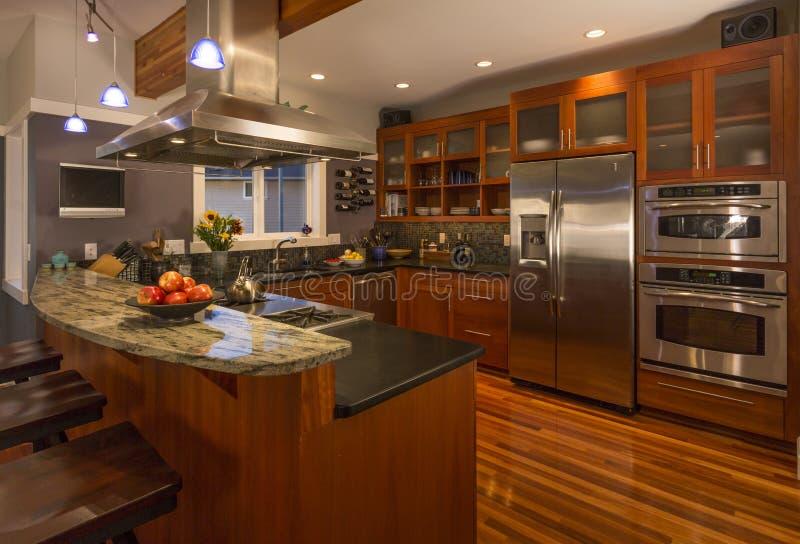 Interior home de gama alta contemporâneo da cozinha com armários e assoalhos de madeira, bancada do granito e dispositivos de aço imagens de stock