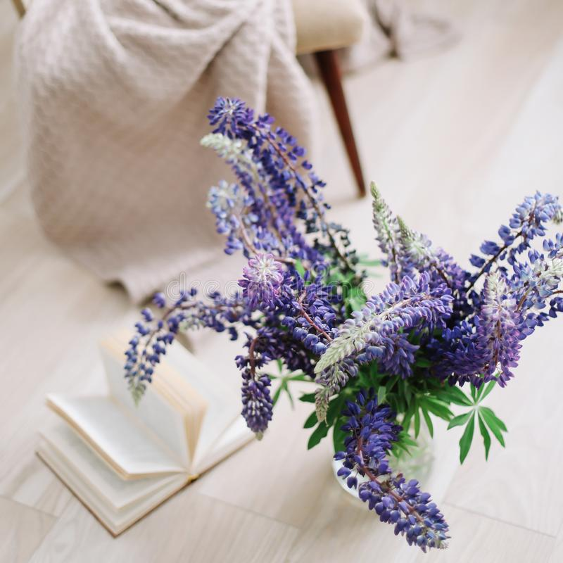 Interior home decor with flowers and books.   Bouquet of purple lupins in a vase in the cozy home interior. Summer floral concept. royalty free stock photos