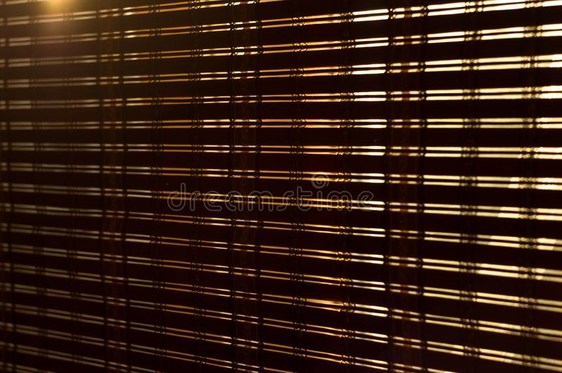The interior of the home, sunlight shining through the bamboo blinds at the window. The interior of the home, sunlight shining through the bamboo blinds at the royalty free stock images