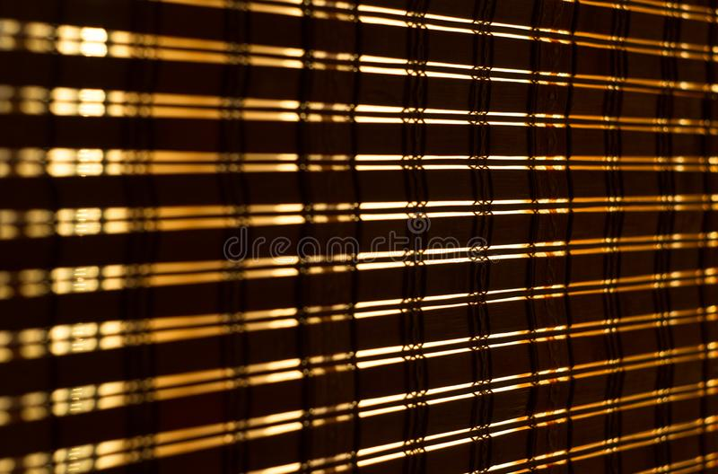 The interior of the home, sunlight shining through the bamboo blinds at the window. Close up stock image