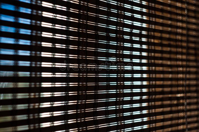 The interior of the home, sunlight shining through the bamboo blinds at the window. Close up royalty free stock photography