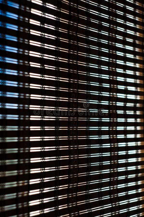 The interior of the home, sunlight shining through the bamboo blinds at the window. Close up royalty free stock image
