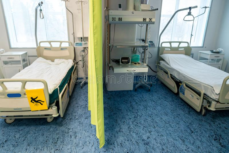 Interior in the hospital, two hospital beds through the curtain, with additional shelves and equipment in the room stock photos