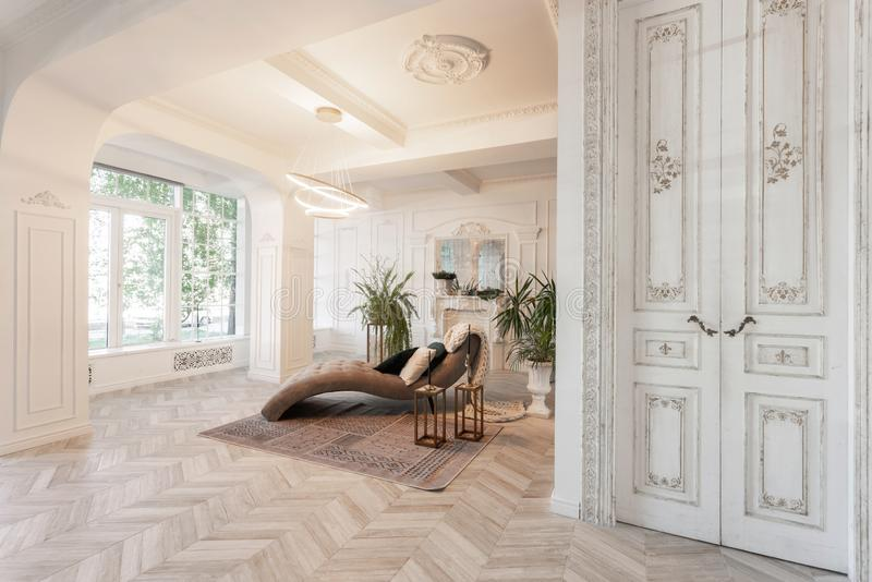 Interior in hotel. daylight in the interior and light of electric lamps. luxury living room with parquet wood floors. Morning in luxurious light interior in the stock photography