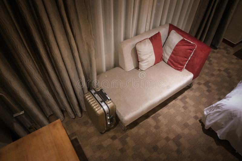 Interior of a hotel room with sofa and luggage. An image of a modern five star hotel master bedroom with a luggage next to sofa.overlooking angle color format stock image