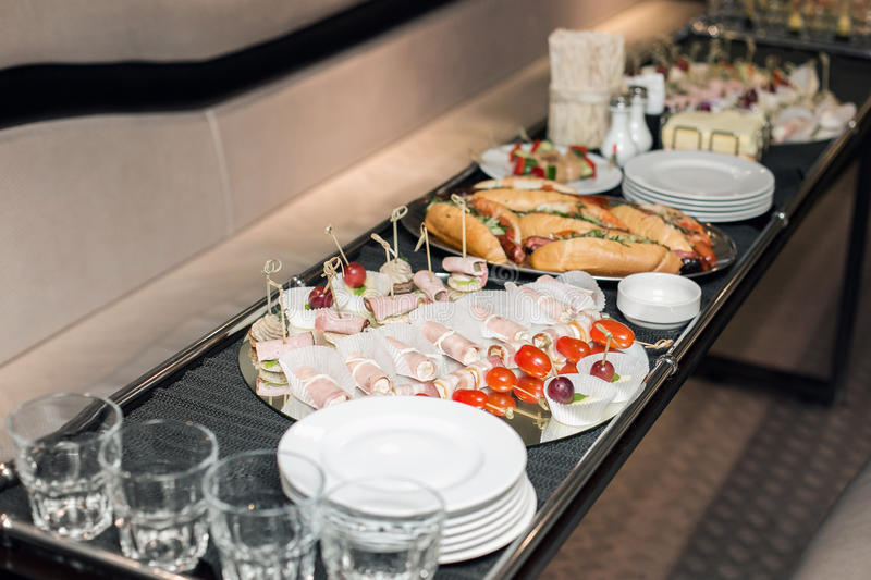 Interior inside the limousine. with sofas and a table covered with snacks for the holiday. Selective focus royalty free stock photography
