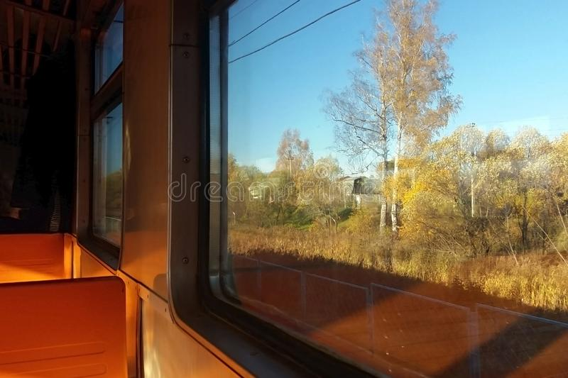 Interior of intercity train with orange plastic seats, window view of a rural autumn landscape stock image