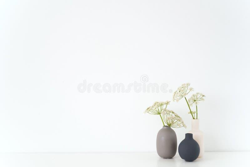 Interior interno moderno Vasos cinzentos, preto e branco com o ramalhete de Aegopodium na tabela no fundo branco Casa macia bonit fotos de stock
